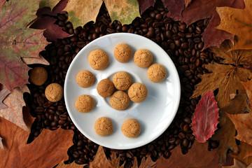 cappucinogebäck auf Kaffeebohnen, Herbstblätter