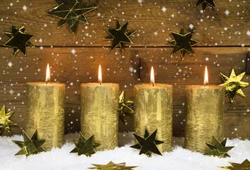 Vier goldene brennende Adventskerzen zum vierten Advent