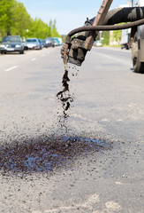 Repairing holes on road by means bitumen and gravel