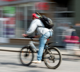 Cyclist in motion riding down the street