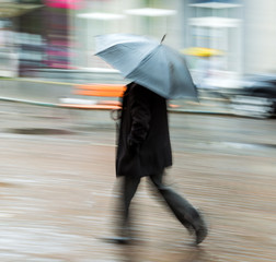 Man walking down the street on rainy day in motion blur