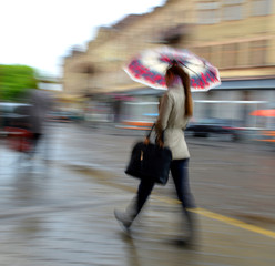 Woman walking in the street on a rainy day