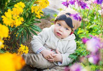 cute baby boy sitting in the flowers