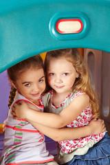 Zwei Mädchen umarmen sich im Kindergarten