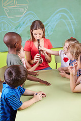 Erzieher spielt Flöte im Kindergarten