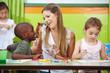 Kindergärtnerin redet mit Junge
