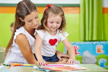 Mädchen bastelt mit Mutter im Kinderzimmer