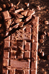 Chopped bar of milk chocolate on wooden background
