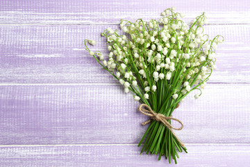 Beautiful lilies of the valley on wooden background