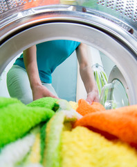 householder woman loading clothing into washing machine