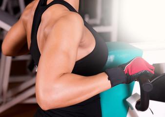 Female body builder using exercise equipment.