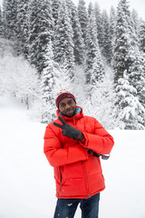 African American Cheerful black man in ski suit in snowy winter