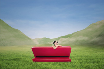 Back shot of red sofa with pensive woman outdoor