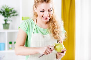 Young woman peeling an apple