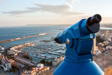 Binoculars telescope overlooking Alicante harbor
