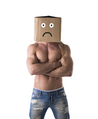 Muscular shirtless bodybuilder with sad box on head