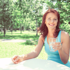 Portrait of young beautiful woman drinking water on picnic
