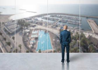 Businessman standing in the room and looking at city
