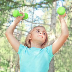 Happy little girl lifting dumbbells in park outdoors