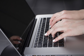 Female hands typing on a keyboard on a laptop.
