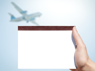 white blank notebook in woman hand and airplane background