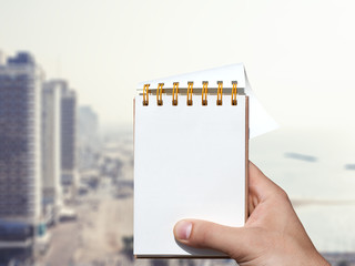 white blank notebook in man hand and resort background