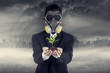 Businessman wearing a gask mask with plant