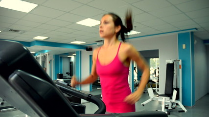 Woman at the gym trains muscles of the shoulders