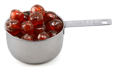Sticky whole glace cherries in a cup measure