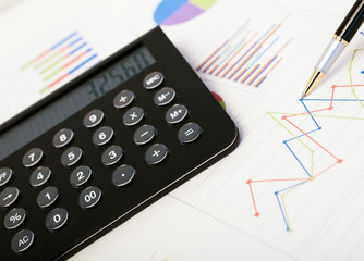 Calculator, pen and business document