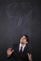Businessman with a storm cloud abouve his head