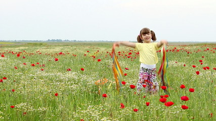 happy little girl waving with colorful ribbons on meadow