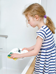 Little girl washing the dishes in the kitchen.