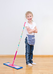Little girl standing near mop at home. Cleaning concept.