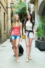 Two cheerfull girls with luggage