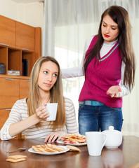 women having quarrel over tea table