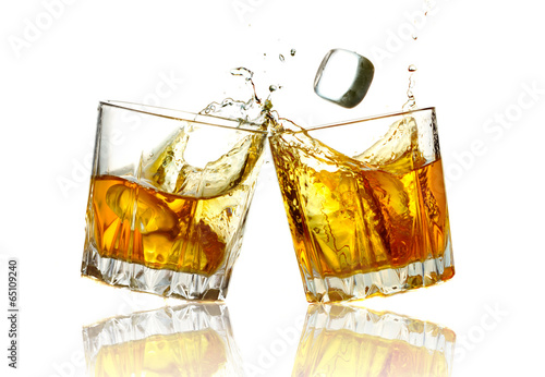 Two whiskey glasses clinking together, isolated - 65109240