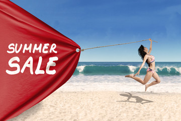 Woman pulling a banner of summer sale