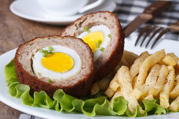 by scotch egg and fried potatoes close-up