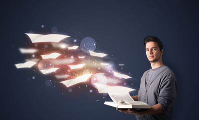 Young guy reading a book with flying sheets coming out of the bo
