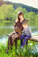 mother and son reading a book by the river