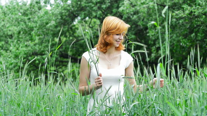 beautiful girl collects wheat ears in the field