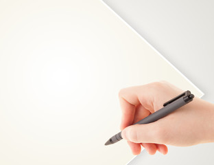 A person writing on a plain blank paper with a balpoint pen