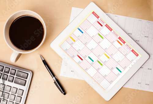Foto op Canvas Koffie Tablet pc showing calendar on screen with a cup of coffee on a d