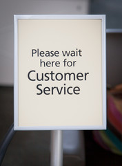 Close-up of a customer service sign