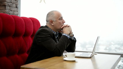 Adult man sitting with a laptop in a cafe near the window.