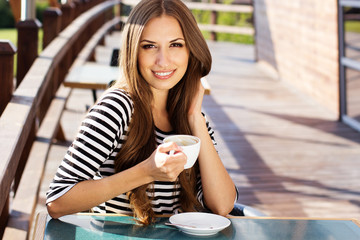 Young woman drinking coffee in a cafe outdoors