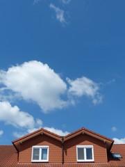 Mansarden mit rotbraunen Schindeln vor Himmel mit Wolken