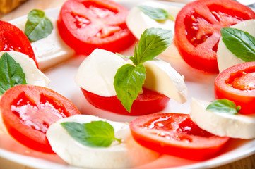 Caprese salad with mozarella cheese, tomatoes, basil