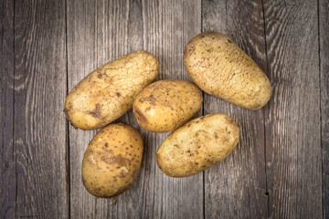 Potatoes on wooden background. Top view.